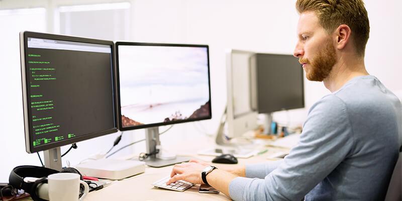 Senior Microsoft Dynamics 365 BC-udvikler sidder foran to skærme og arbejder