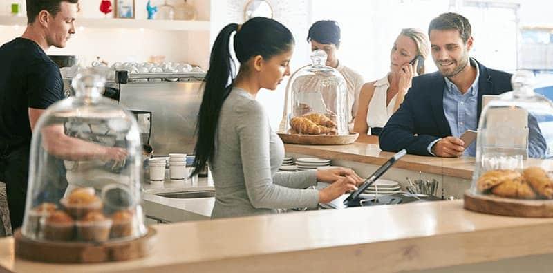 Kvinde på café betjener en kunde ved POS kassesystemet NP Restaurant