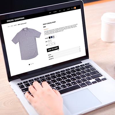 Person kigger på trøje på bærbar i webshop