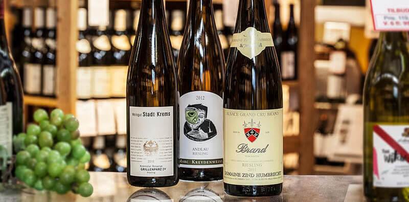 Tre vinflasker og en klasse vindruer