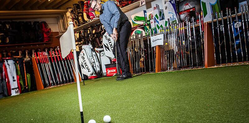 To golfbolde tæt på golfhul på kunstgræs