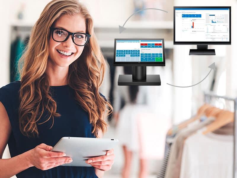 Smilende kvinde med lyst hår, briller og holder en tablet, og to computerskærme i baggrunden