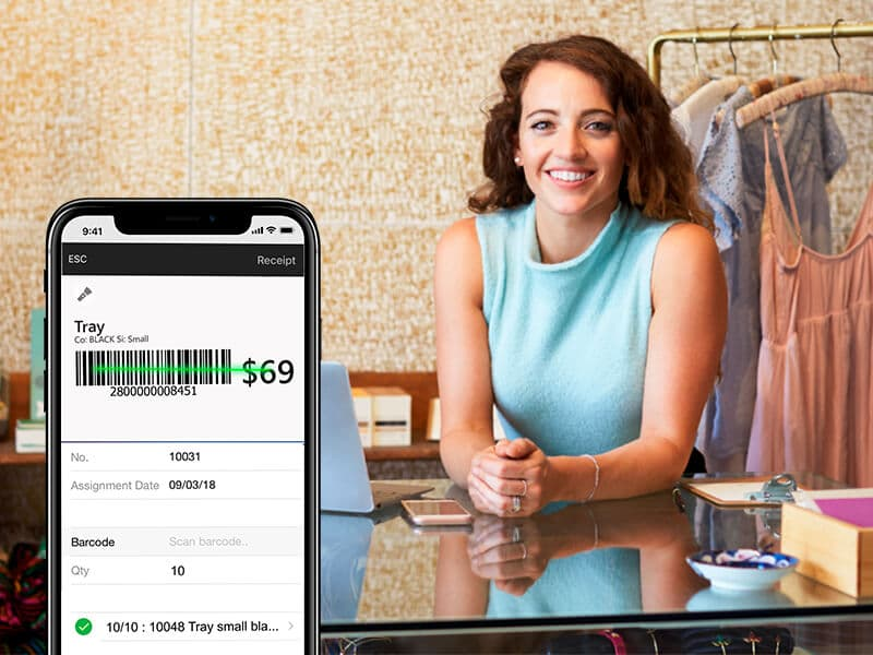 En mobil med en stregkode på skærmen og en kvinde siddende i baggrunden
