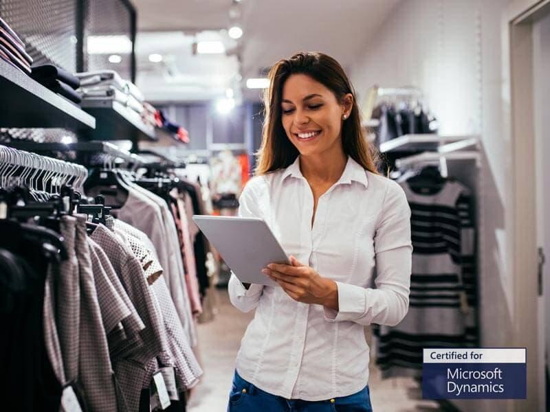 Kvinde står med tablet med Microsoft Dynamics i tøjbutik