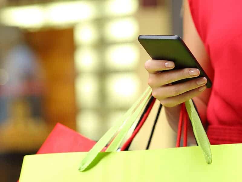 Kvinde med shopping poser under armen og holder en mobil i hånden hvor hun læser om detailhandel i 2017