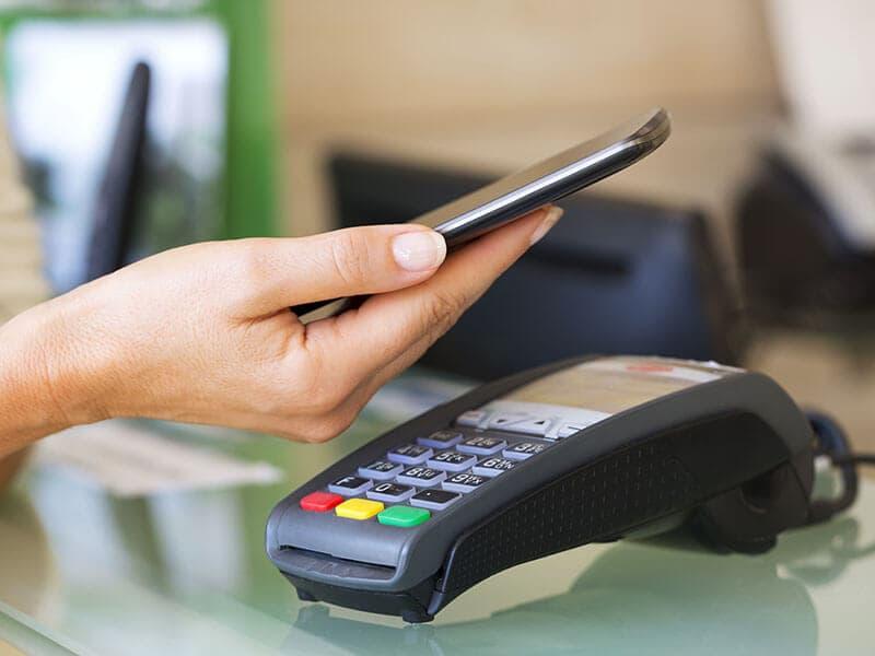 Person betaler med kontaktløs funktion på dankortmaskine