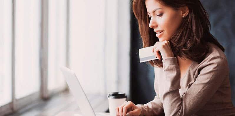 Kvinde holder kreditkort og sidder foran bærbar og køber ind på omnichannel webshop