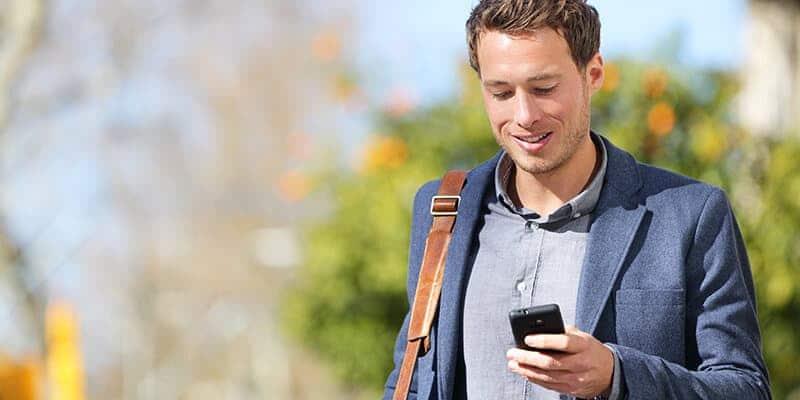 Mand går udenfor og får en besked fra NaviPartners SMS-afsenderen