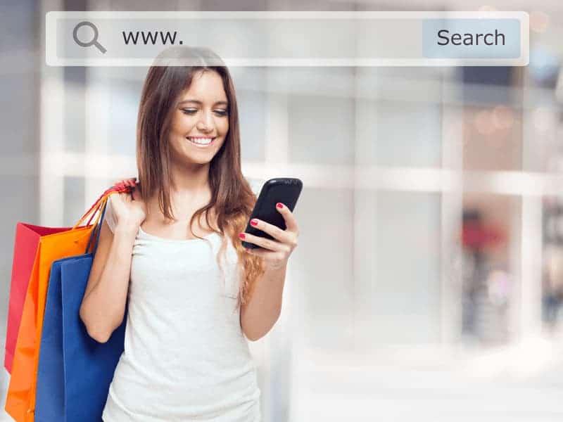 Kvinde med shopping poser som kigger på sin mobil og smiler