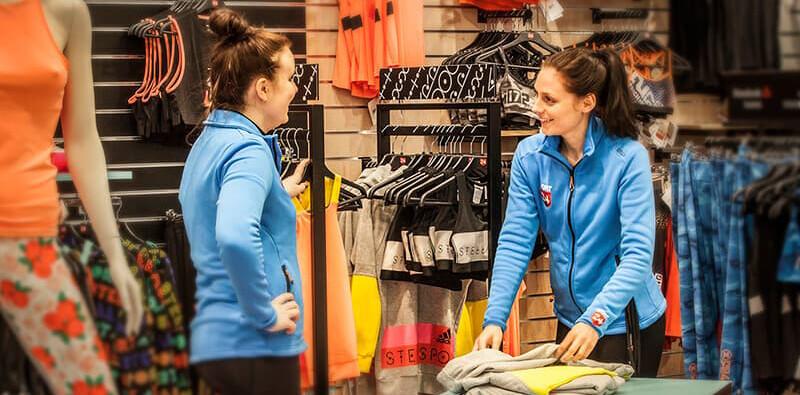 To kvindelige medarbejdere i blåt tøj smiler