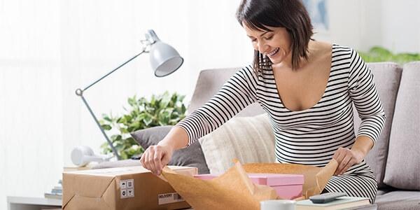 Kvinde pakker en pakke op hun har bestilt online