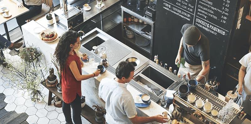 Café vist oppefra i fugleperspektiv med to kuner og to personale der anvender POS-system