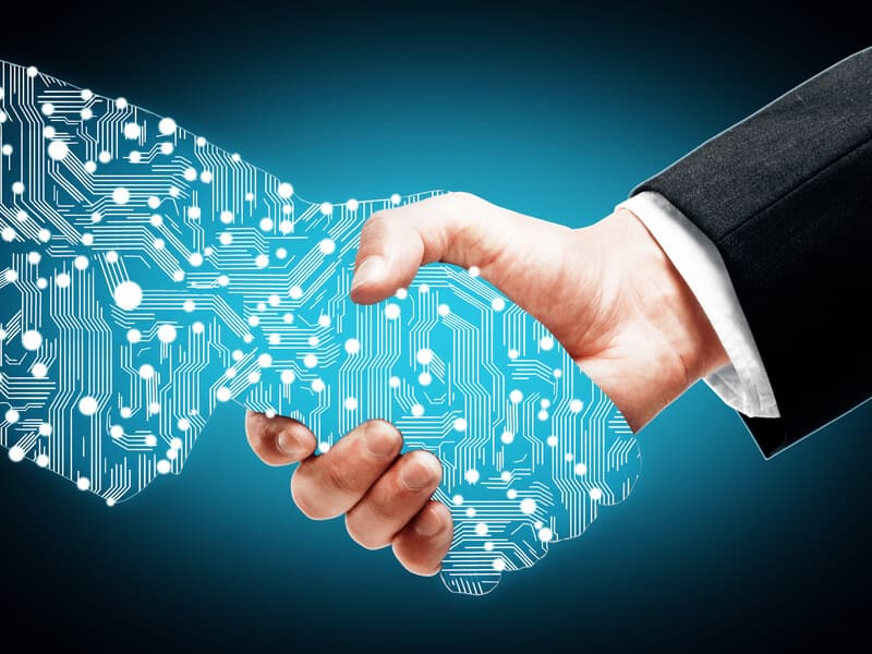 Håndtryk hvor den ene hånd består af en masse hvide streger og cirkler som skal illustrerer digital transformation og forbundet data