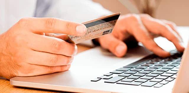 Person sidder foran sin computer med et kreditkort i hånden og afprøve nogle af vores ekstra webshop-funktioner