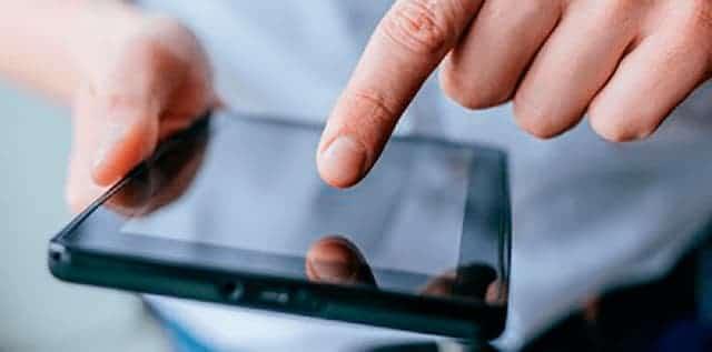 Person holder en tablet og trykker på skærmen