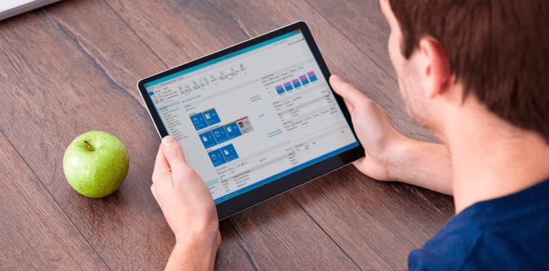 Microsoft Dynamics NAV vist på tablet som holdes af mand som sidder med ryggen til kameraet og et grønt æble ved bordet