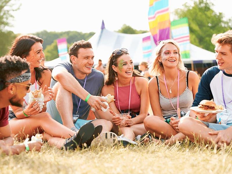 Tre mænd og tre kvinder der sidder i græsset og spiser mad i solskin