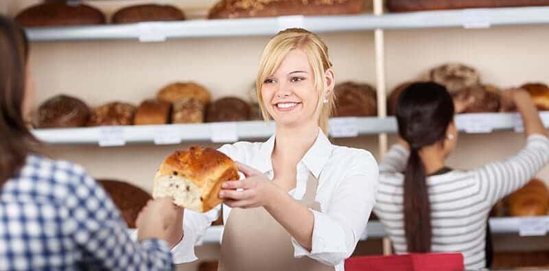 Kvindelig bager holder et brød op foran en kunde