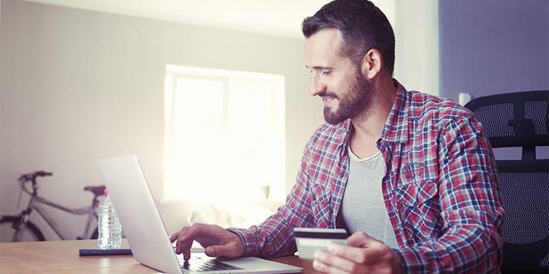 Mand sidder foran bærbar med kreditkort og afprøver Navi Connect og Expense Management