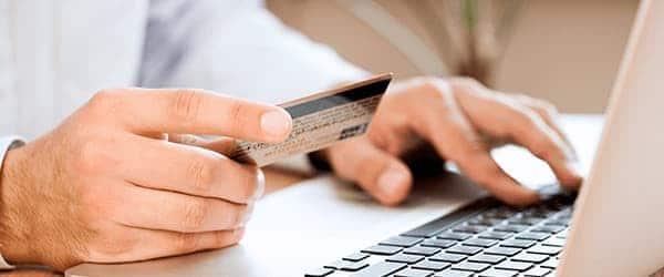 Mand med kreditkort foran bærbar