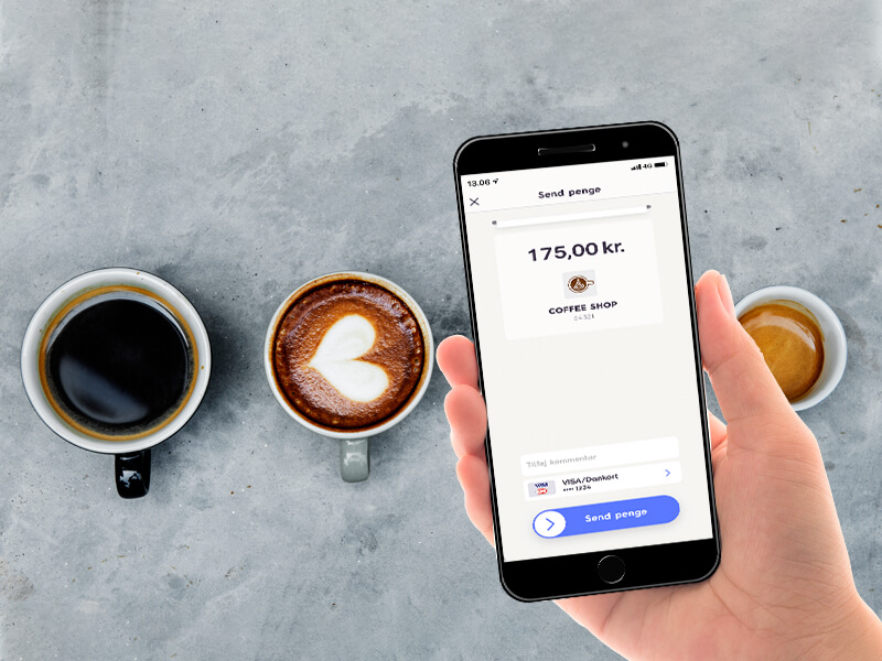 Kunde på café betaler for sin kaffe med MobilePay