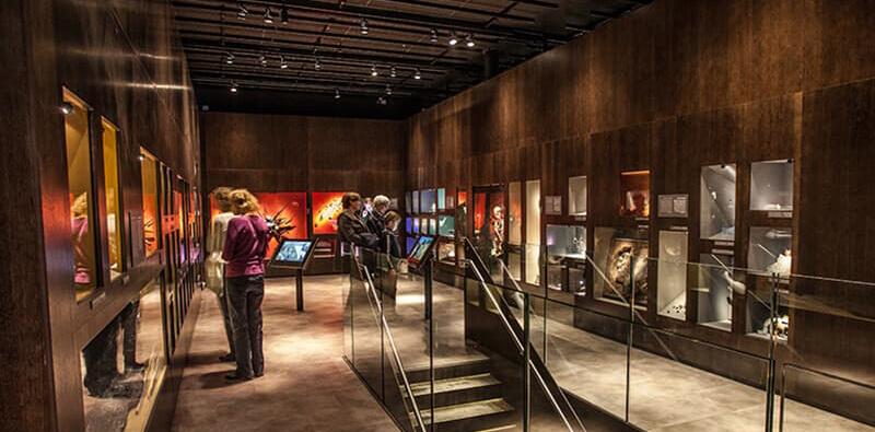 Mørkt rum med udstilling og turister indenfor i Moesgaard Museum