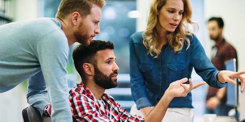Retail-konsulent sidder og arbejder med to kollegaer