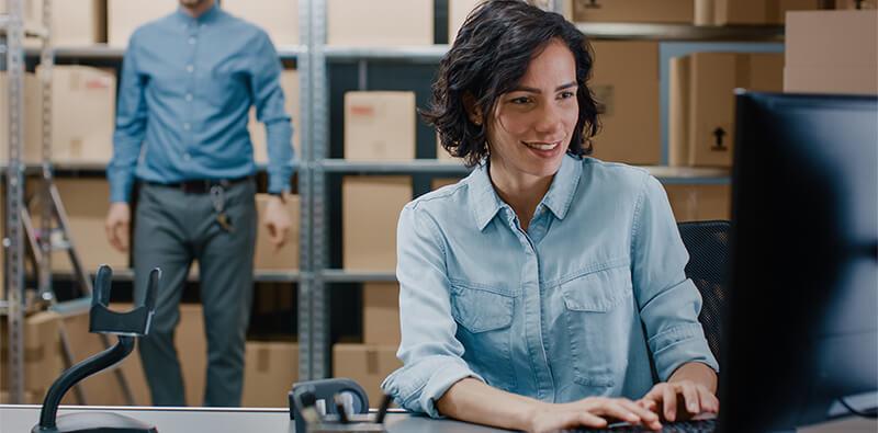 Kvinde sidder ved computer og opretholder et opdateret lager med RFID lagerstyring