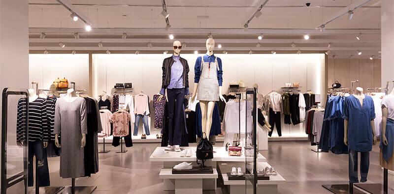 Tøjbutik uden mennesker med to mannequiner i midten