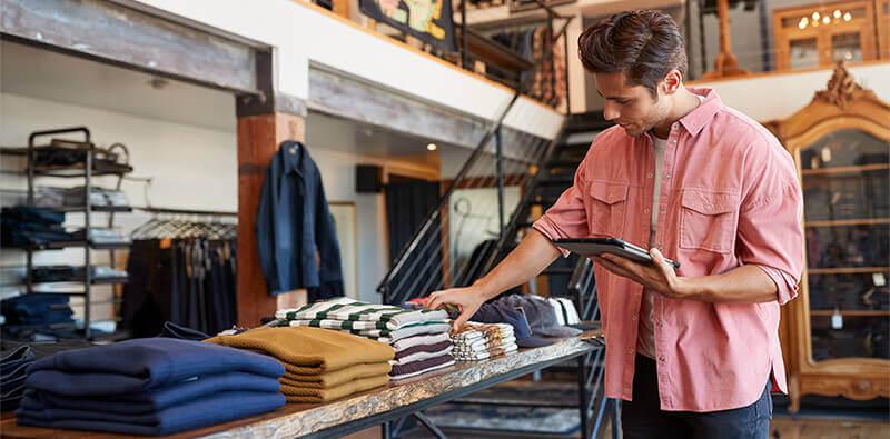 Ung mand i tøjbutik tjekker lagerbeholdning med en tablet