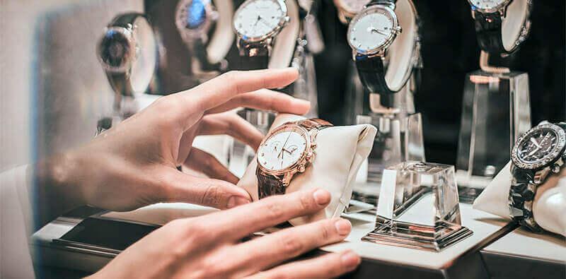 Kvinde sætter ur i montre